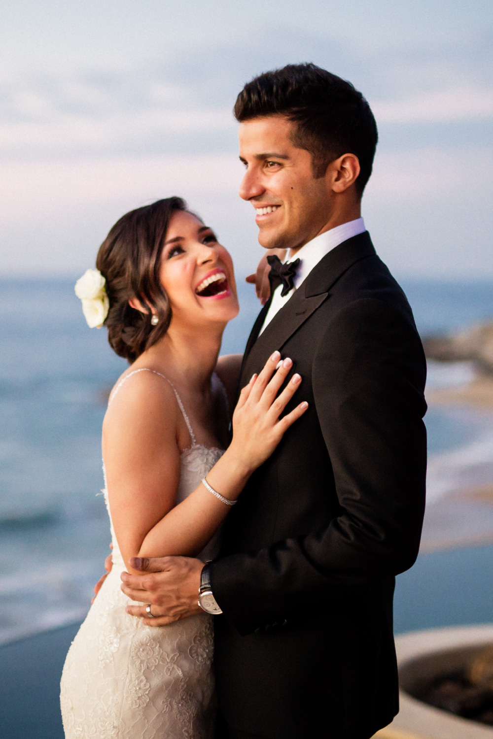 bride and groom holding each other on their wedding day in front of the pacific ocean