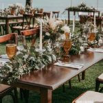 Large wooden tables with greenery and pampas grass with among candles and glassware for a destination wedding reception in mexico