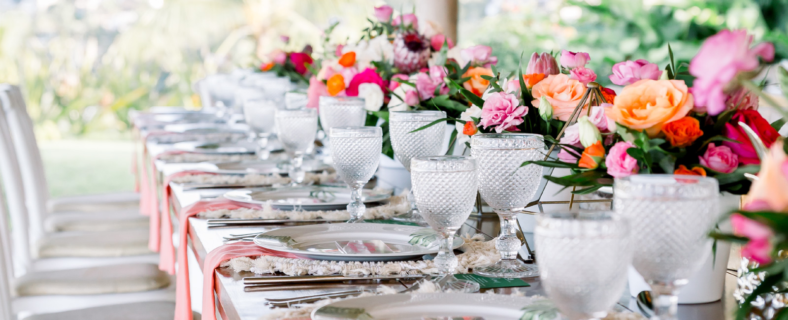Wine glasses and colorful florals on a long table with china outside in the gorgeous weather of mexico