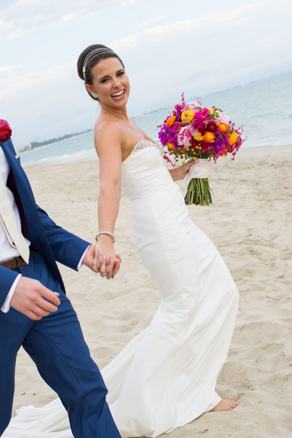bride and groom walk on beach with colorful bouquet and blue suit at destination wedding in puerto vallarta mexico