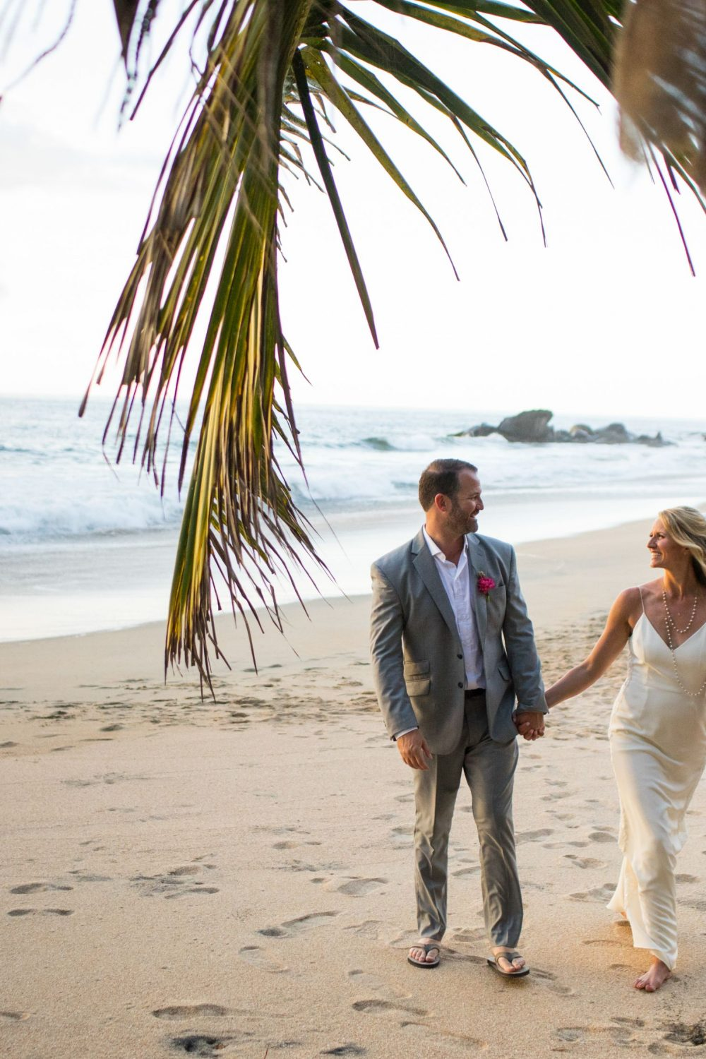 Two Marriers walking on the sandy beach of Mexico the day of their Destination Wedding