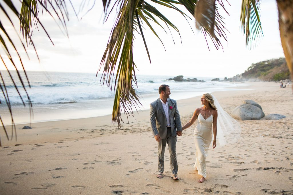 Two marriers walking on the Beach in Mexico the day of their destination wedding with palm branches and rocks in the background