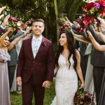 Bride and groom pose with their wedding party holding moody bouquets at their destination wedding in Punta Mita, Mexico