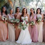 Beautiful bride in white dress with sweetheart neckline stands on the beach with her bridesmaids and holds moody wedding bouquets at her destination wedding in Sayulita, Mexico