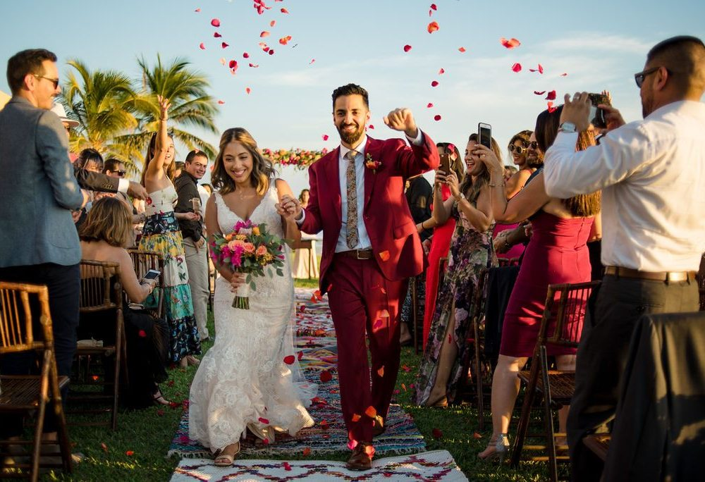 bride and groom leave the ceremony under a shower of rose petals at this Punta Mita Mexico destination wedding