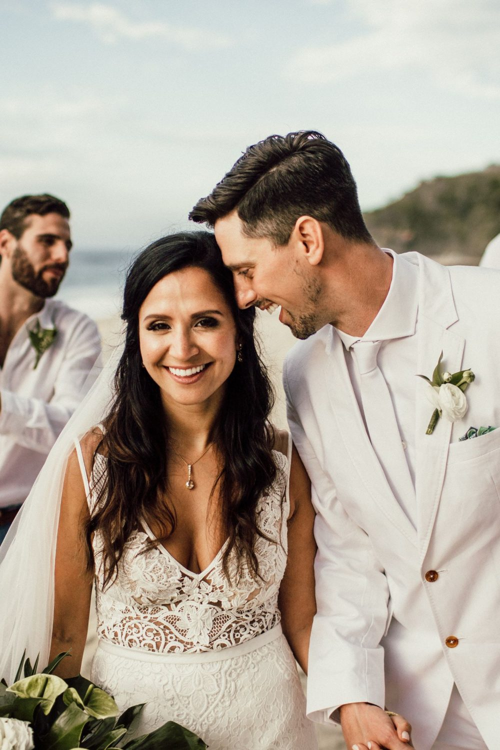 bride and groom laugh and walk with their wedding party on the beach at this Sayulita Mexico destination wedding