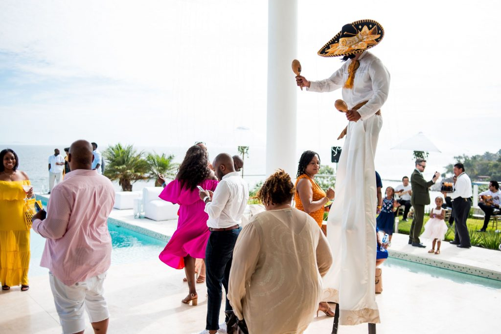guests mingle and sip cocktail while mariachi on stilts entertain them at this Punta Mita Mexico destination wedding