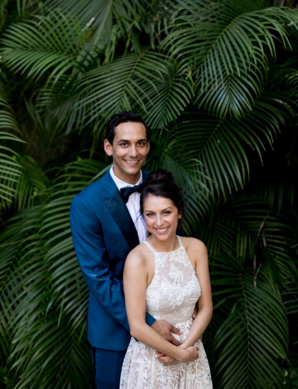 The bride and groom in a blue suit stand in front of jungle palm trees for a photo before the ceremony at this Sayulita destination wedding