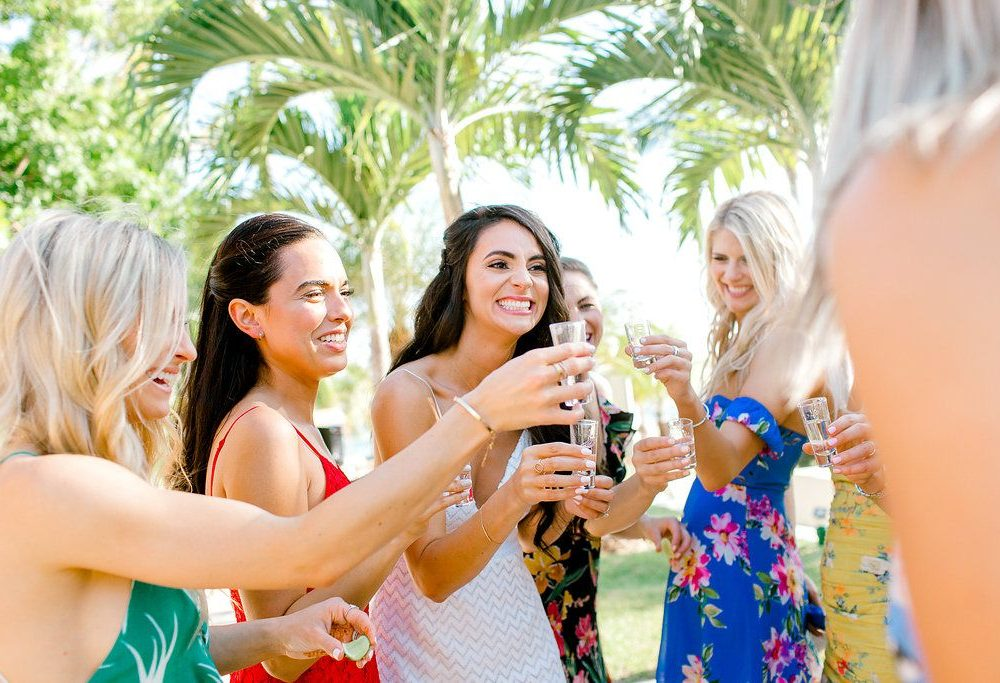 the bride smiles during a tequila toast with her tribe at this chic Punta Mita Mexico rehearsal dinner