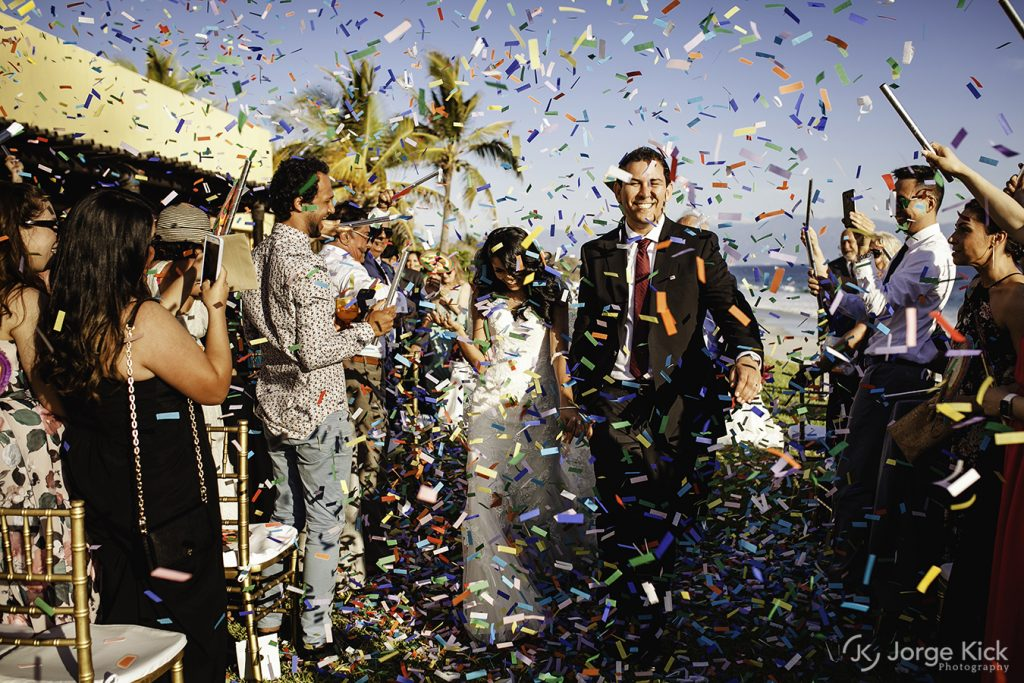 The bride and groom depart their ceremony with huge smiles celebrating beneath a shower of biodegradable confetti at this Punta Mita Mexico destination wedding