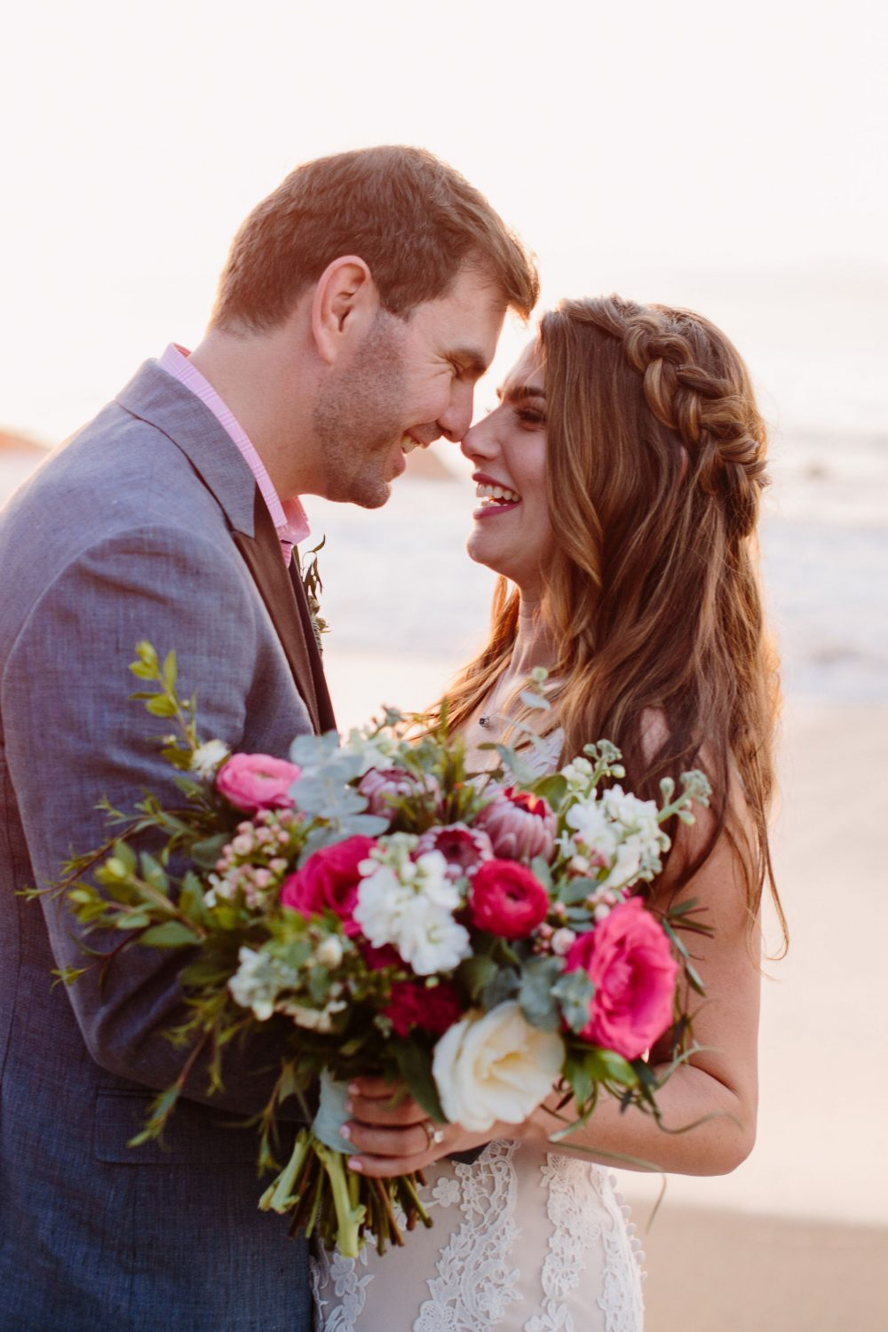 he bride with a boho braid hairstyle and a beautiful pink white and greenery bouquet stands with her groom on the beach at this Sayulita Mexico destination wedding