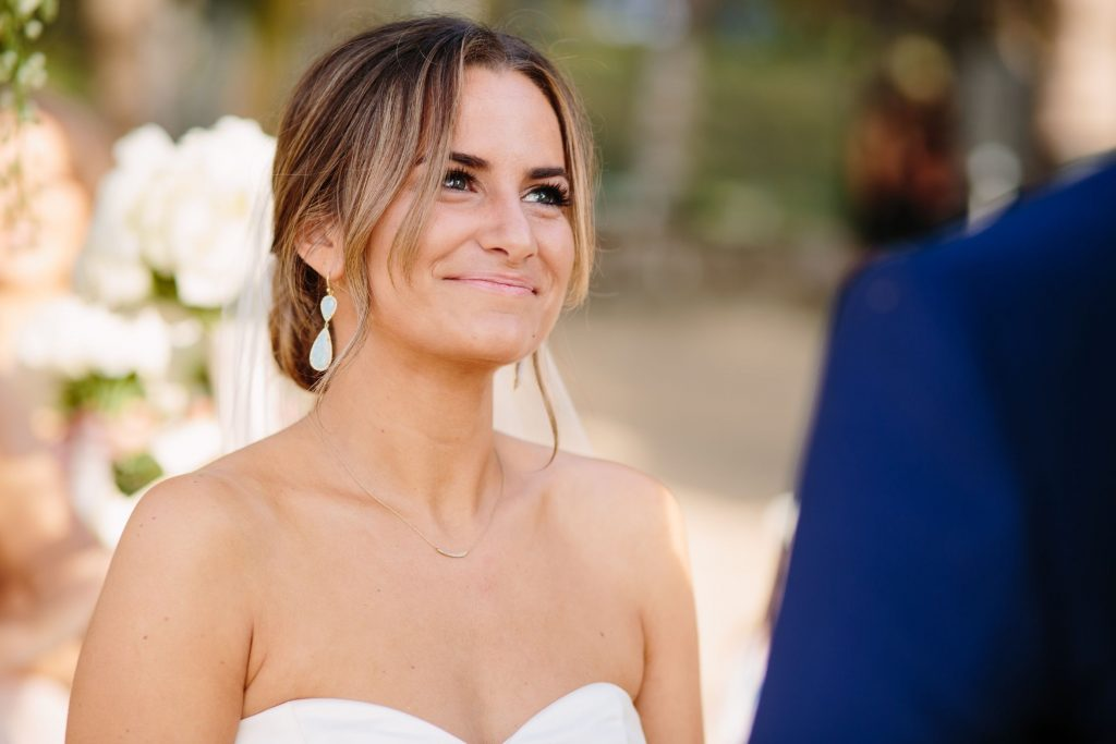 The bride smiles at the groom as she listens to his personal vows during the Sayulita Mexico destination wedding ceremony