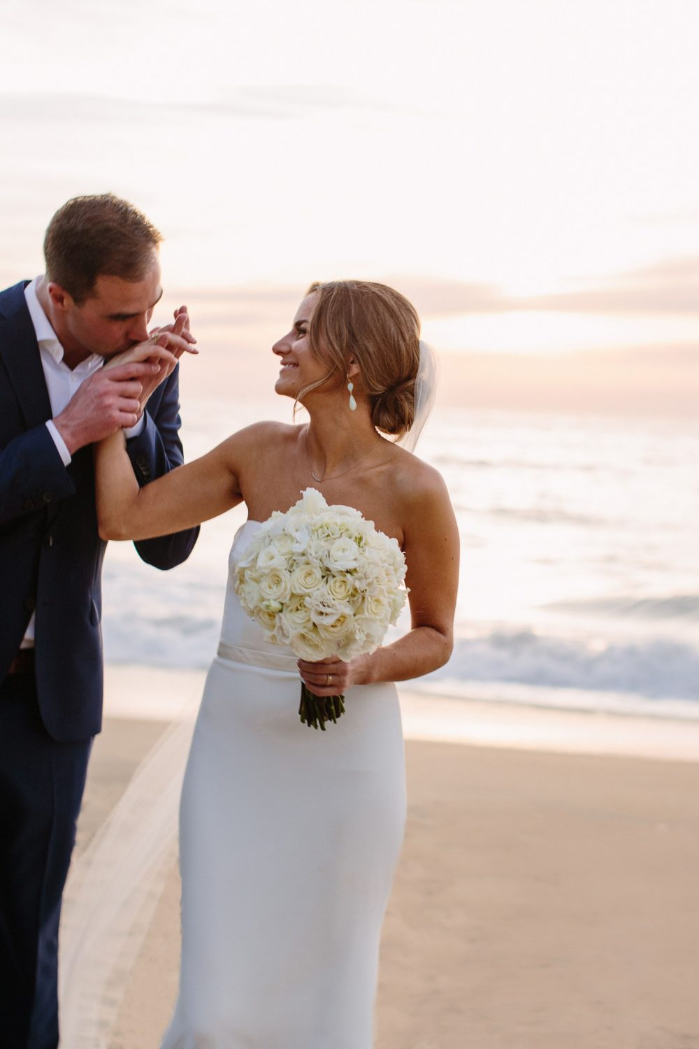 groom kisses bride's hand on the beach at sunset at this Sayulita Mexico destination wedding