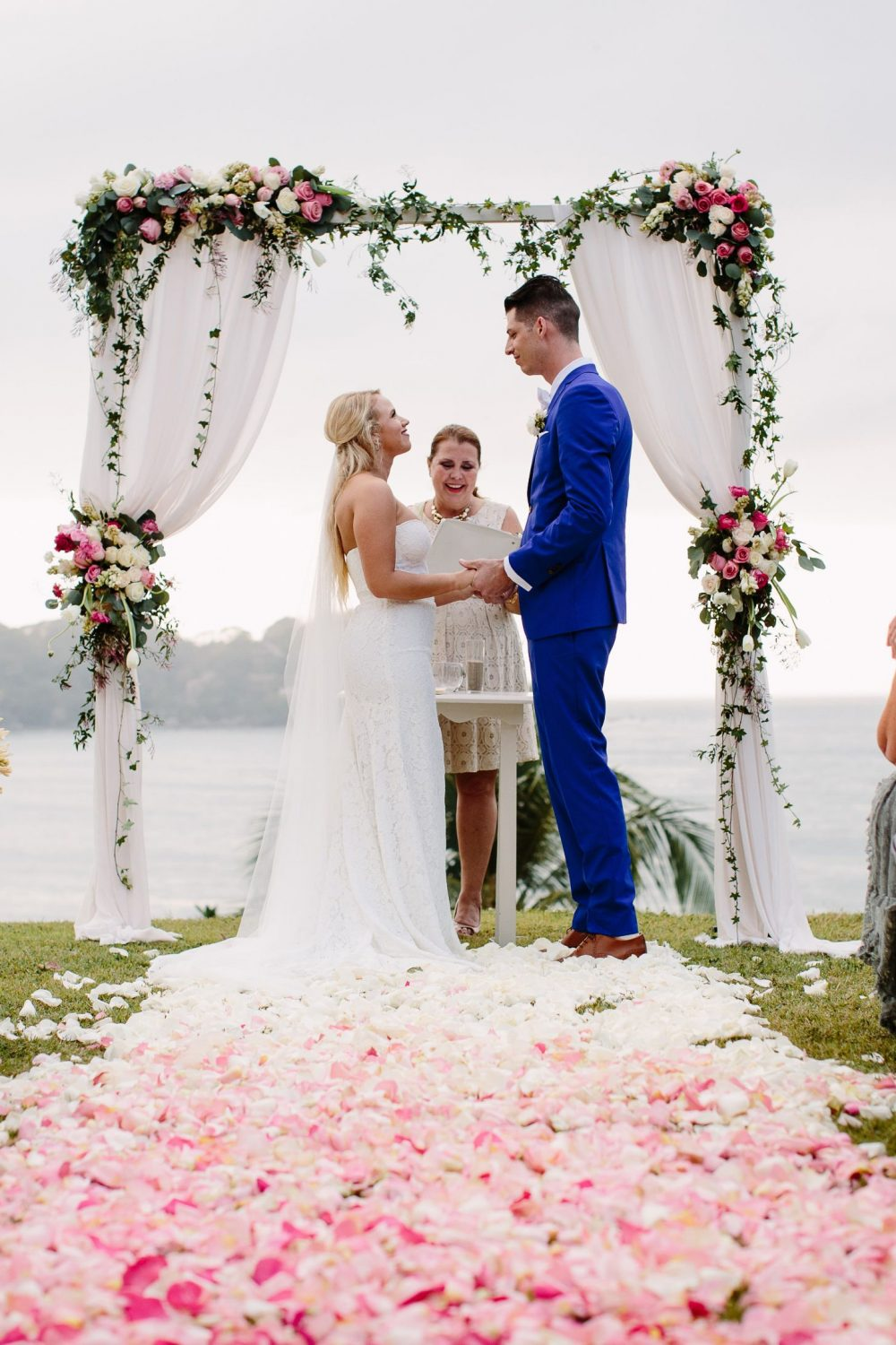 the bride and groom during their wedding ceremony with an arch wtih white curtains, greenery and pink and white flowers at this Sayulita Mexico destination wedding