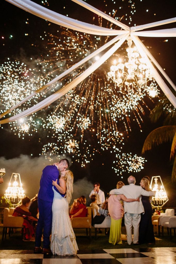 Fireworks explode behind a kissing bride and groom on the dance floor at this Sayulita Mexico destination wedding