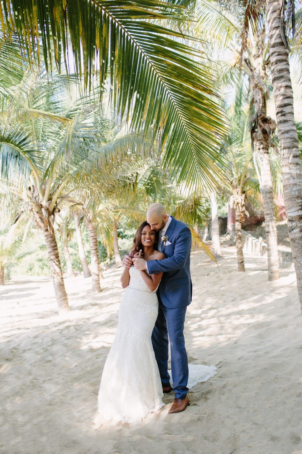 the bride and groom hug on the beach under the palm trees during their first look at this Sayulita Mexico destination wedding