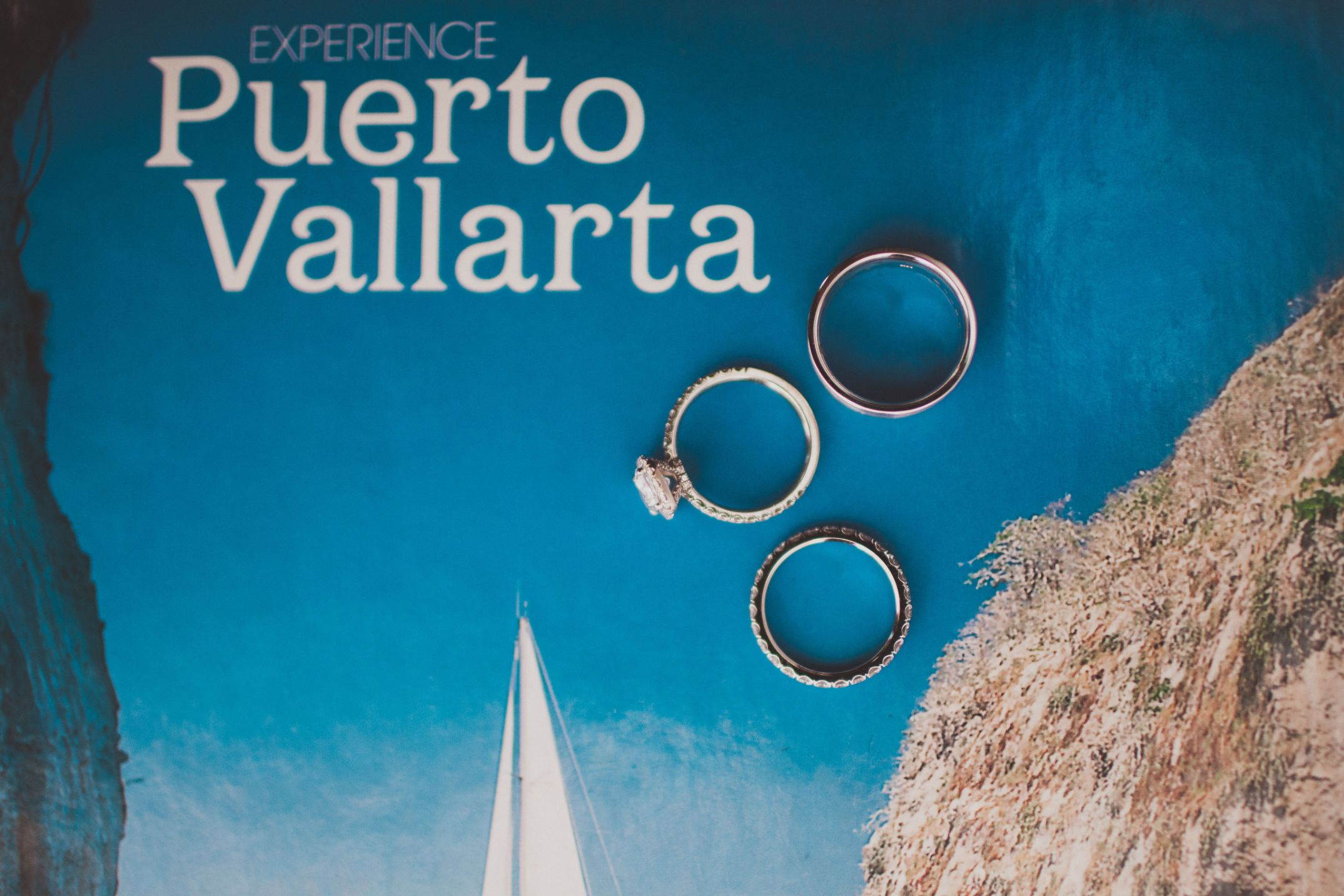 The wedding rings are set on a Puerto Vallarta tourism book for a creative photo at this destination wedding