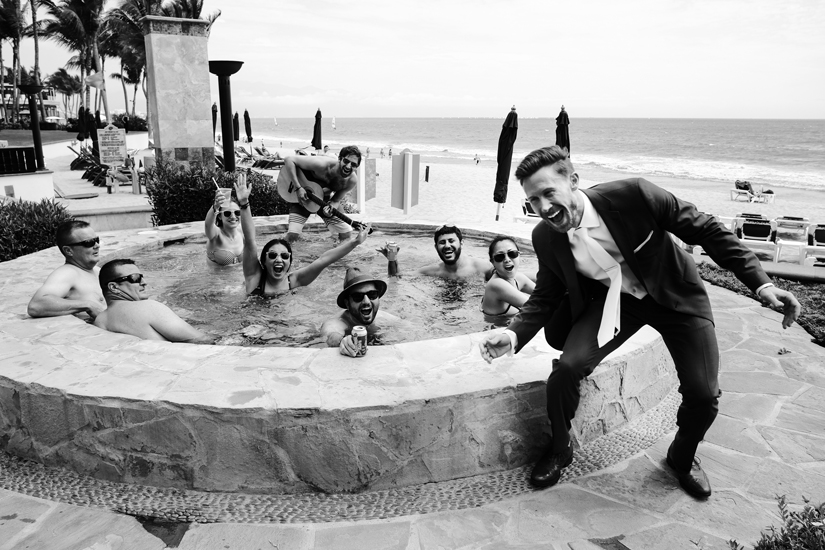The groom poses with hotel guests enjoying the whirlpool before this Puerto Vallarta Mexico destination wedding.