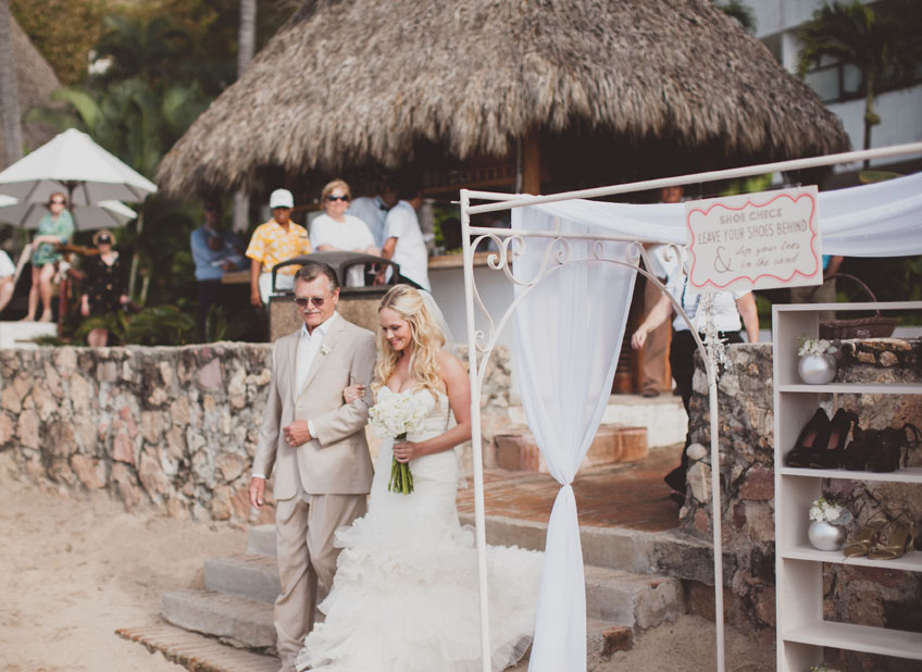 The bride walks down the aisle as hotel guests look on at this Puerto Vallarta Mexico destination wedding