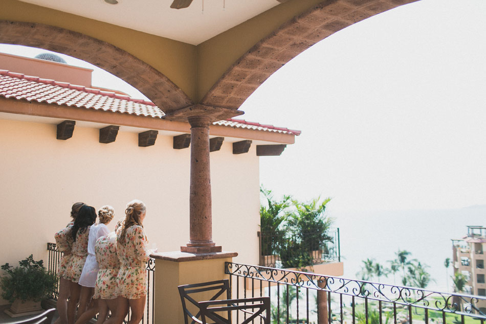 The bride and her bridesmaids look out over the balcony at this beautiful hotel in Nuevo Vallarta Mexico, home to a destination wedding group.