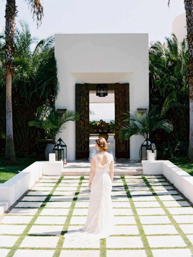 The bride posts in front of a stunning villa at her destination wedding in Punta Mita Mexico
