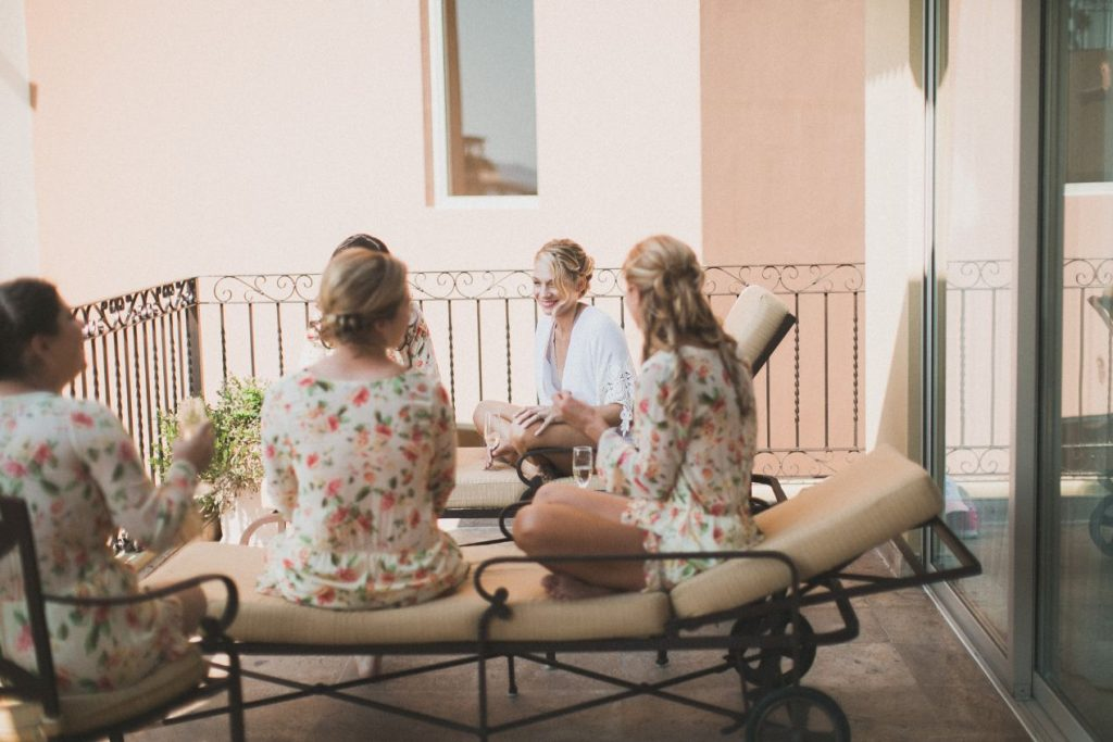 A bride sits with her girlfriends soaking in the beauty of destination wedding day in Puerto Vallarta Mexico.